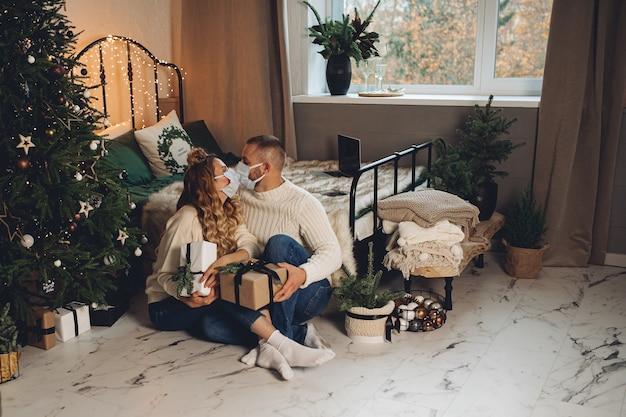 Glückliches junges paar, das schutzmasken trägt und geschenkboxen am heiligabend hält
