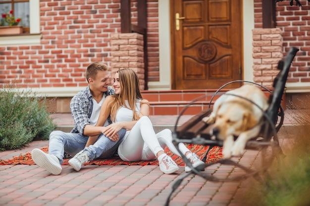 Glückliches junges paar, das sich amüsiert und am deckenteppich vor dem haus sitzt. der hund schläft auf der bank