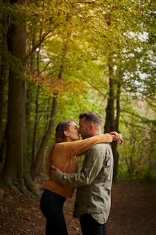 Glückliches junges paar, das sich auf einem schönen weg in einem wald küsst