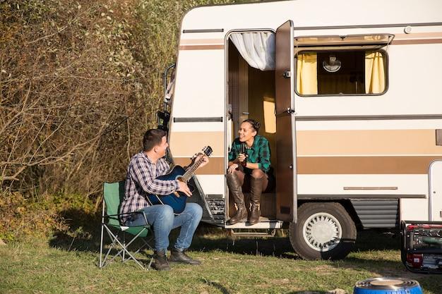 Glückliches junges paar, das sich mit seinem retro-wohnmobil in den bergen entspannt. freund, der für seine freundin auf der gitarre spielt.
