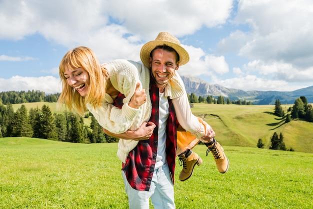 Glückliches junges paar, das spaß hat, huckepack auf einer schönen grünen wiese zu tun