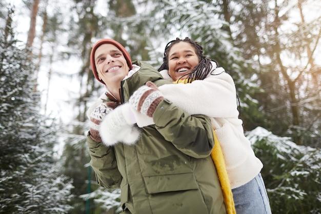 Glückliches junges paar, das spaß zusammen während ihres spaziergangs im winterwald hat