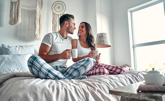 Glückliches junges paar, das spricht und lacht, während es auf dem bett sitzt und morgens zu hause kaffee trinkt.