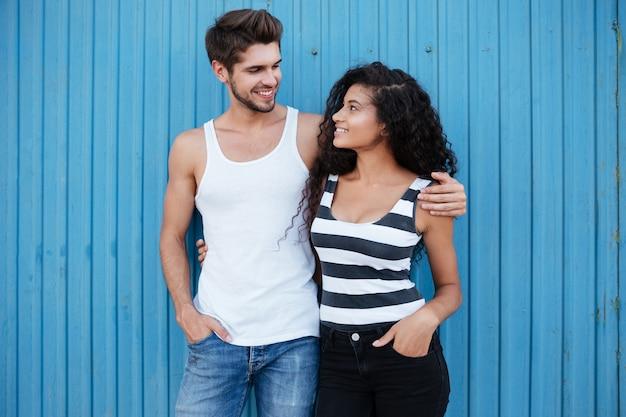 Glückliches junges paar, das über blauer wand steht und umarmt
