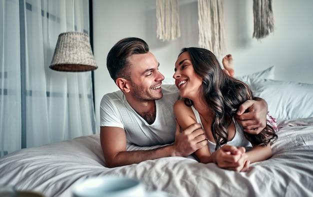 Glückliches junges paar, das umarmt und lächelt, während auf dem bett in einem schlafzimmer zu hause sitzt.