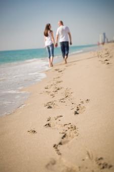 Glückliches junges paar, das während ihrer flitterwochen an einem tropischen strand spazieren geht