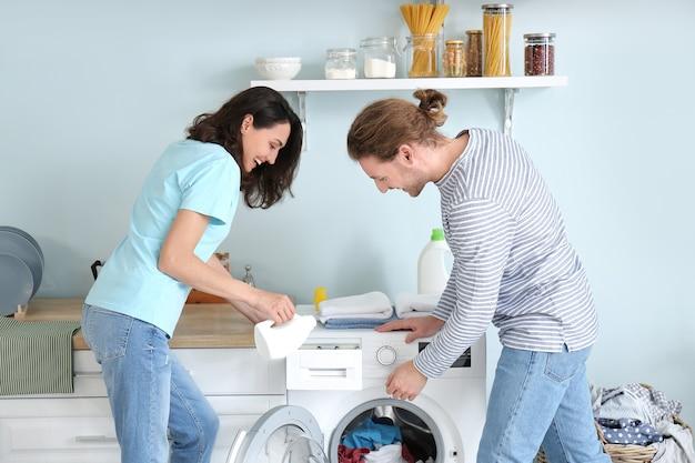 Glückliches junges paar, das wäsche zu hause macht