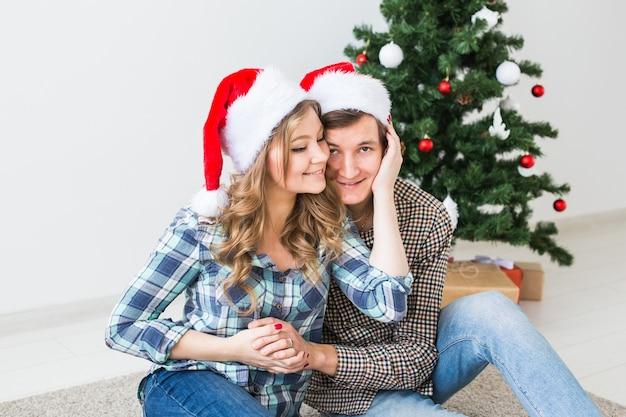 Glückliches junges paar, das weihnachten zu hause feiert.