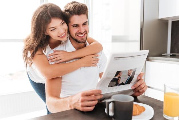 Glückliches junges paar, das zeitung auf der küche umarmt und liest