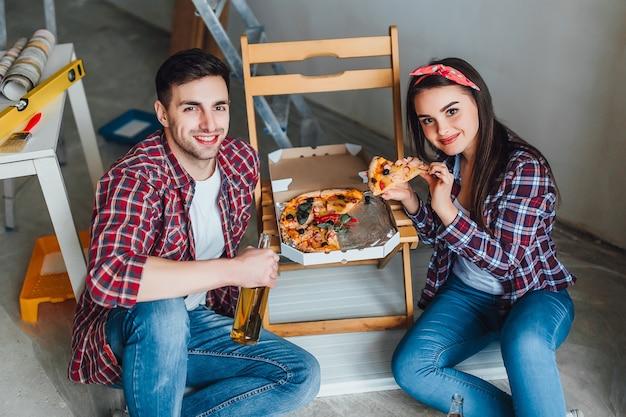 Glückliches junges paar, das zu hause reparaturen durchführt und romantische zeit zum pizzaessen hat?