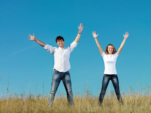 Glückliches junges paar, das zusammen auf sommerwiese mit den händen oben steht
