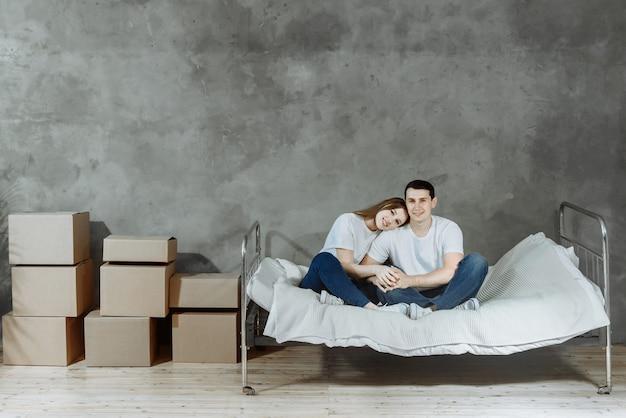 Glückliches junges paar familienvater und frau sitzen auf dem bett und umarmen sich am tag des umzugs im wohnzimmer