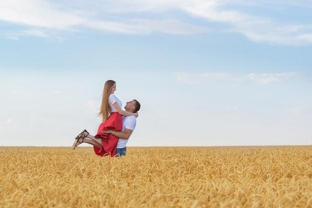 Glückliches junges paar haben spaß im weizenfeld am sonnigen sommertag. ein mann hält geliebte in seinen händen