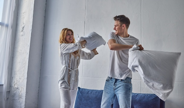 Glückliches junges paar hat spaß im schlafzimmer. die gesellschaft miteinander genießen. beim kissenschlacht aufs bett springen