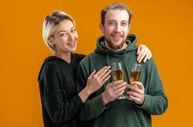 Glückliches junges paar im freizeitkleidungsmandat mit gläsern des champagners und der fröhlichen frau, die breit lächelnd valentinstag über orange wand steht