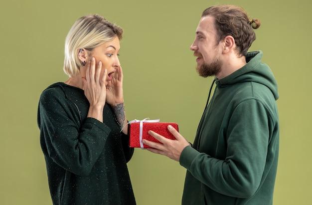 Glückliches junges paar im freizeitkleidungsmann mit geschenk für seine reizende lächelnde und überraschte freundin, die valentinstag feiert, der über grüner wand steht