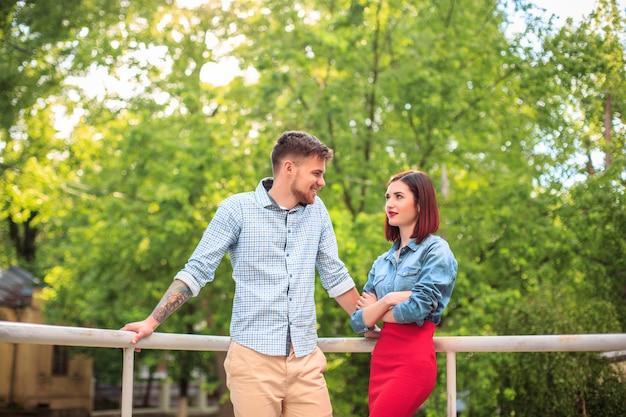 Glückliches junges paar im park stehend und lachend am hellen sonnigen tag