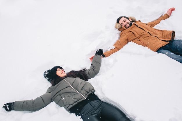 Glückliches junges paar im winter. familie draußen. mann und frau, die aufwärts schauen und lachen. liebe, spaß, jahreszeit und leute - gehend in winterpark. im neuschnee liegen, schneeengel zum spaß bringen