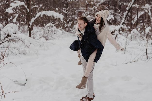 Glückliches junges paar im winterpark, das spaß hat. familie im freien. liebe.