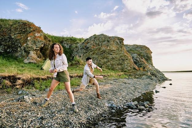 Glückliches junges paar in den stiefeln, in den shorts und in den hemden, die steine im wasser werfen, während sie auf flussufer auf hintergrund der felsen stehen