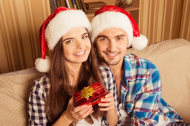 Glückliches junges paar in den weihnachtsmützen, die ein weihnachtsgeschenk halten