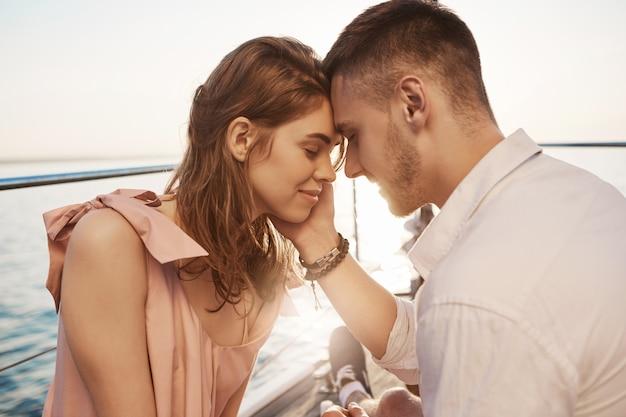 Glückliches junges paar in der liebe lächelnd und bootsfahrt auf dem meer genießend. romantik und urlaubskonzept. freund berührt zärtlich ihre wange und freundin fühlt schmetterlinge im bauch