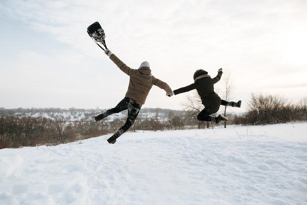 Glückliches junges paar in der liebe springt für freude. kalter tag des verschneiten winters. winter liebesgeschichte.
