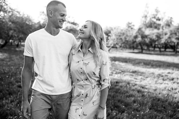 Glückliches junges paar in der liebesumarmung genießt frühlingstag, liebend sorglos zusammen draußen im park spazierend