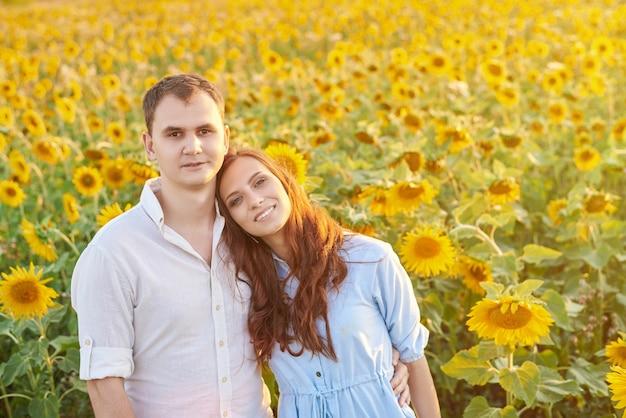Glückliches junges paar in einem sonnenblumenfeld