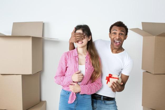 Glückliches junges paar in einer neuen wohnung. mann, der überraschungsgeschenk zur frau gegen ausgepackte kisten gibt.