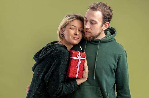 Glückliches junges paar in freizeitkleidung mann und frau mit geschenk, das glücklich in der liebe zusammen umarmt, valentinstag feiern, der über grüner wand steht