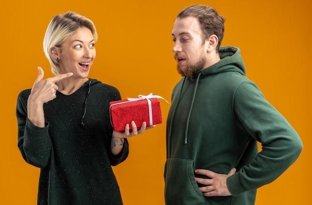 Glückliches junges paar in freizeitkleidung mann und lächelnde frau mit geschenk, das mit zeigefinger auf ihren freund zeigt, der valentinstag feiert, der über orange wand steht