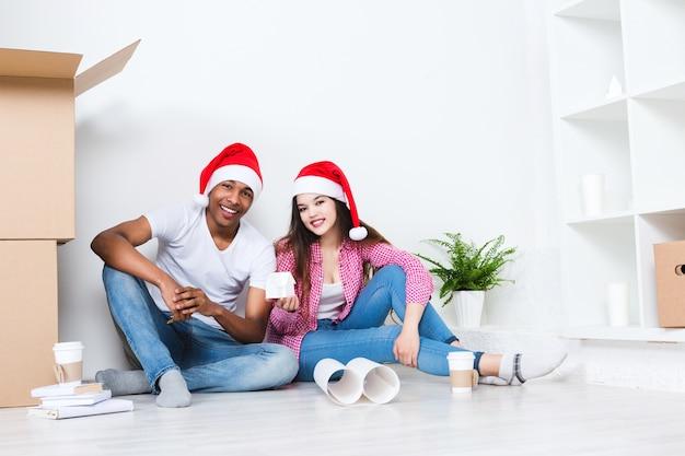 Glückliches junges paar in weihnachtsmützen im neuen haus