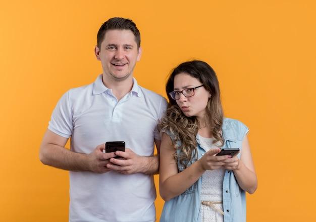 Glückliches junges paar mann und frau mit gadgets lächelnd über orange wand