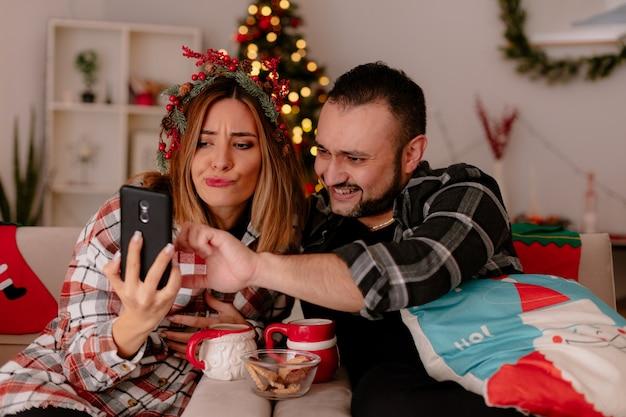 Glückliches junges paar mann und frau sitzen auf einer couch mit tassen tee, die spaß mit smartphone im dekorierten raum mit weihnachtsbaum im hintergrund haben