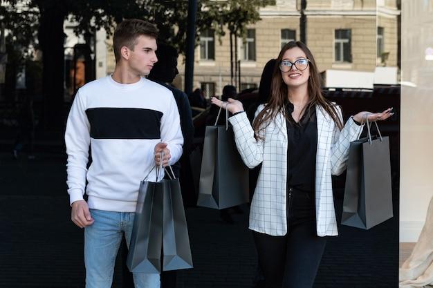 Glückliches junges paar mit einkäufen nach erfolgreichem einkaufen. schwarzer freitag. kerl und mädchen mit einkaufstüten neben der vitrine.