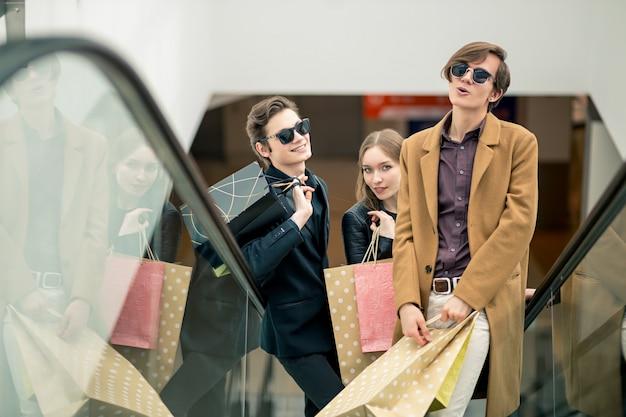 Glückliches junges paar mit einkaufstüten, die durch rolltreppe hinuntergehen und finger im einkaufszentrum zeigen