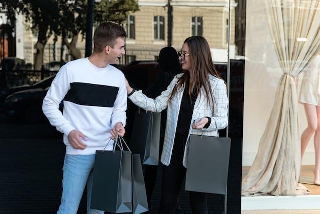 Glückliches junges paar mit einkaufstüten im einkaufszentrum. kerl und mädchen über schaufenster. schwarzer freitag. einkaufen.