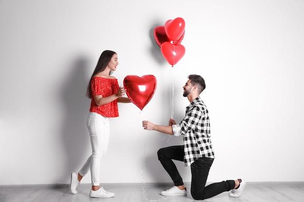 Glückliches junges paar mit herzförmigen ballons in der nähe der hellen wand. valentinstag feier