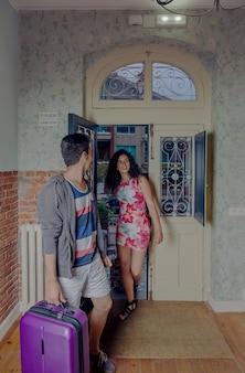 Glückliches junges paar mit koffern, die in der herberge ankommen, um einen urlaub zu genießen. urlaub und tourismuskonzept.