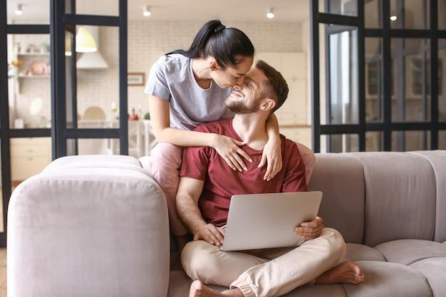 Glückliches junges paar mit laptop zu hause