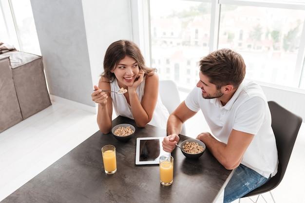 Glückliches junges paar mit leerem bildschirmtablett, das frühstück auf der küche hat