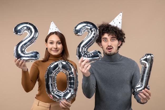 Glückliches junges paar mit neujahrshut wirft für kamera-mädchen auf und kerl mit und auf grau