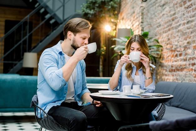 Glückliches junges paar mit pässen und eintrittskarten, am tisch sitzend und kaffee trinkend, vor der reise. hotellobby-café, wartehalle