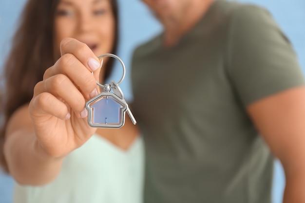 Glückliches junges paar mit schlüssel von ihrem neuen haus, nahaufnahme