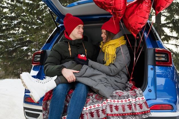 Glückliches junges paar mit valentinstag oder geburtstagsgeschenk