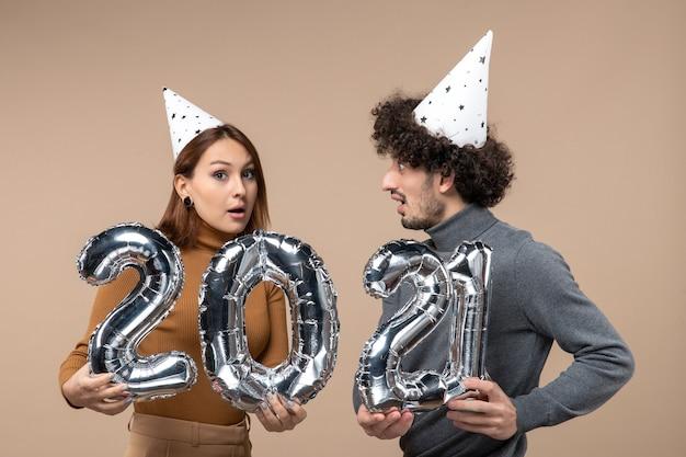 Glückliches junges paar mit verwirrtem gesichtsausdruck tragen neujahrshut posiert für kameramädchen