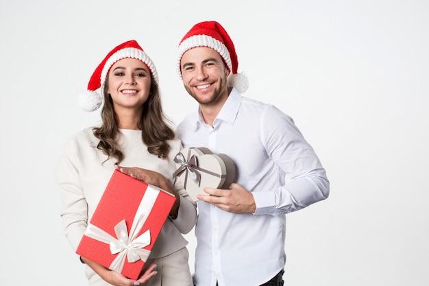 Glückliches junges paar mit weihnachtsgeschenk auf weißem hintergrund.