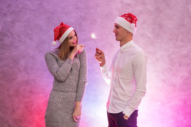 Glückliches junges paar mit weihnachtsmütze und weihnachtswunderkerzen studioaufnahme.