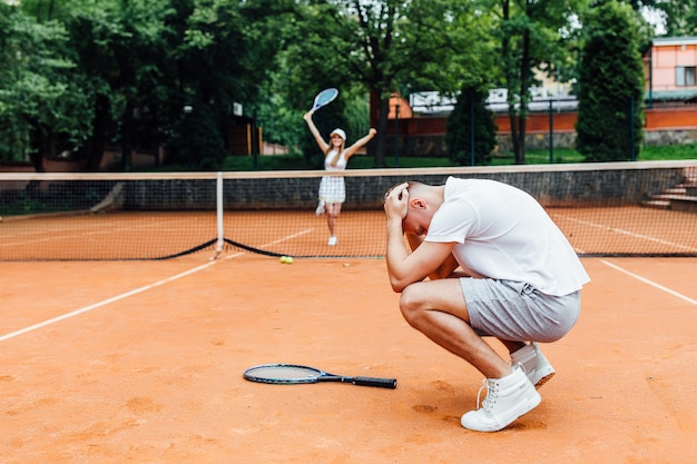 Glückliches junges paar tennis spielen spiel im freien mann verloren und frau so glücklich.